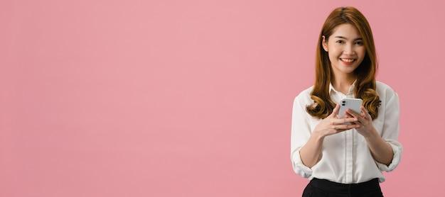 Удивленная молодая азиатская дама с позитивным выражением лица пользуется мобильным телефоном, широко улыбается, одета в повседневную одежду и смотрит в камеру на розовом фоне.