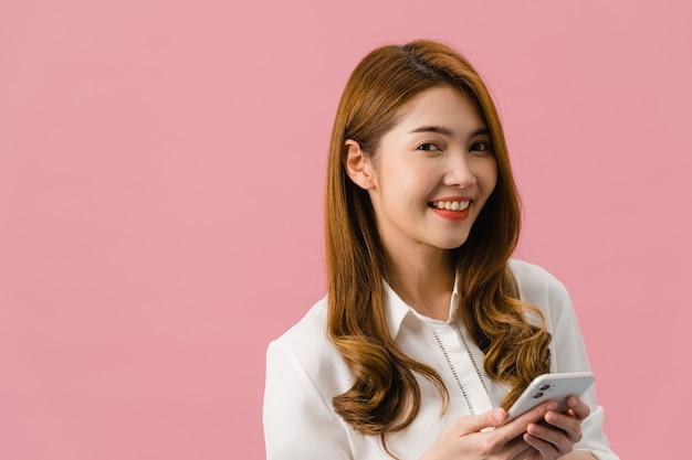 긍정적 인 표정으로 휴대 전화를 사용하여 놀란 젊은 아시아 아가씨는 광범위하게 미소 짓고 캐주얼 한 옷을 입고 분홍색 배경에 카메라를보고 있습니다.