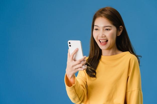 肯定的な表情で携帯電話を使用して驚いた若いアジア女性、広く笑顔、カジュアルな服を着て、青い背景に分離されて立っています。幸せな愛らしい喜んで女性は成功を喜ぶ。