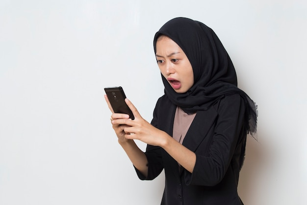 Surprised young asia muslim woman using mobile phone on white background