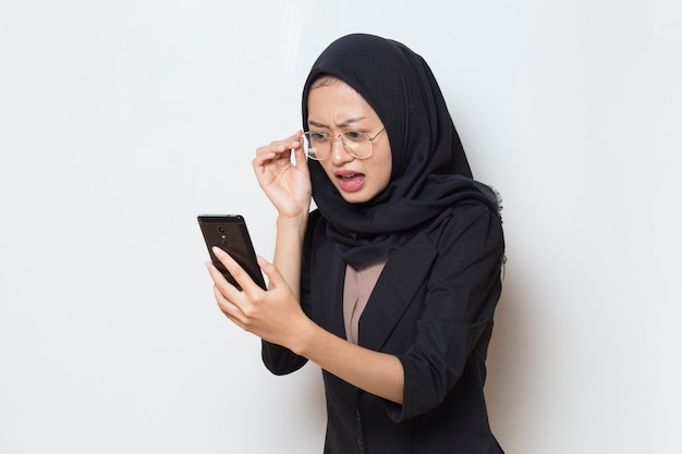 Surprised young asia muslim woman with glasses using mobile phone on white background