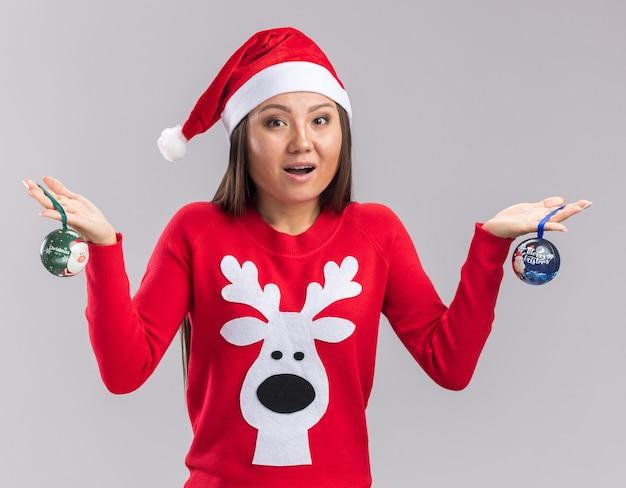 Удивленная молодая азиатская девушка в новогодней шапке со свитером, держащая елочные шары на белом фоне