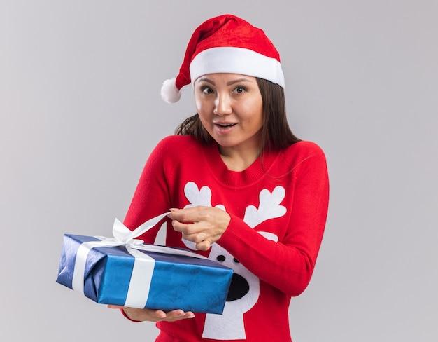 Удивленная молодая азиатская девушка в рождественской шапке со свитером, держащей подарочную коробку на белом фоне