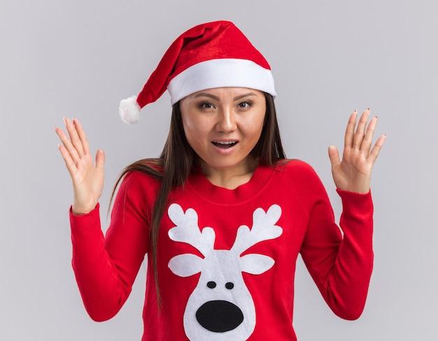 흰색 배경에 고립 된 크기를 보여주는 스웨터와 크리스마스 모자를 쓰고 놀란 된 젊은 아시아 여자