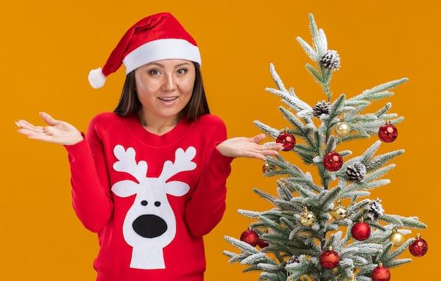 Удивленная молодая азиатская девушка в новогодней шапке со свитером стоит рядом с елкой, разводя руками, изолированными на оранжевой стене