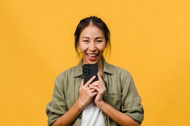 ポジティブな表情で携帯電話を使用し、広い笑顔で、カジュアルな服を着て、黄色い壁のカメラを見て驚いた若いアジアの女性。幸せな愛らしい嬉しい女性は成功を喜んでいます。