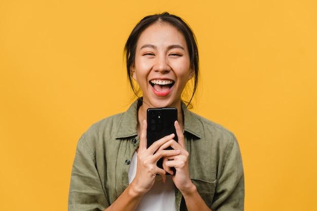 黄色い壁にカジュアルな服を着て、前向きな表情で携帯電話を使って驚いた若いアジアの女性。幸せな愛らしい嬉しい女性は成功を喜んでいます。