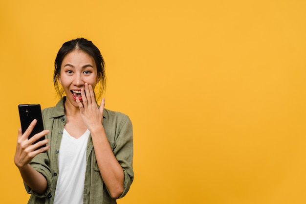Surprised young asian lady using mobile phone with positive expression, smiles broadly, dressed in casual clothing and stand isolated on yellow wall. happy adorable glad woman rejoices success.