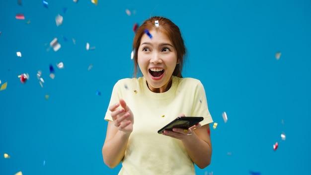 ポジティブな表情の携帯電話を使って驚いた若いアジア人女性は、紙吹雪の雨の下でカジュアルな服を着て、青い壁で祝うために、広く笑顔を見せます。幸せな嬉しい女性は成功を喜ぶ。