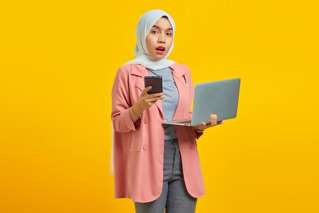 파란색 배경에 휴대폰과 노트북을 들고 놀란 젊은 아시아 여성