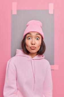 La giovane donna asiatica sorpresa con le labbra increspate della pelle sana fissa la telecamera rimanendo impressionata da qualcosa che indossa un cappello con cappuccio casual posa in studio con un foglio di carta intonacato per la tua promozione