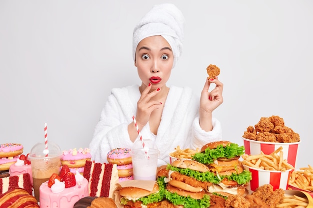 Surprised young asian woman with red lips manicure eats junk food containing much calories surrounded by hamburgers cakes and fizzy drinks