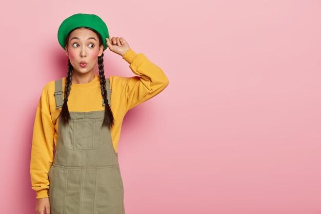 Giovane donna asiatica sorpresa con labbra arrotondate, trucco minimo tocca il berretto e guarda da parte con stupore