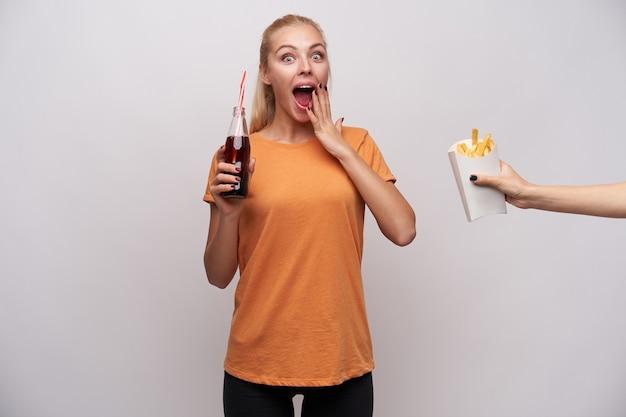 Удивленная молодая привлекательная голубоглазая блондинка смотрит в камеру с широко открытыми глазами и открытым ртом, держа в руке бутылку содовой и взволнованная тем, что кто-то угощает ее картофелем фри