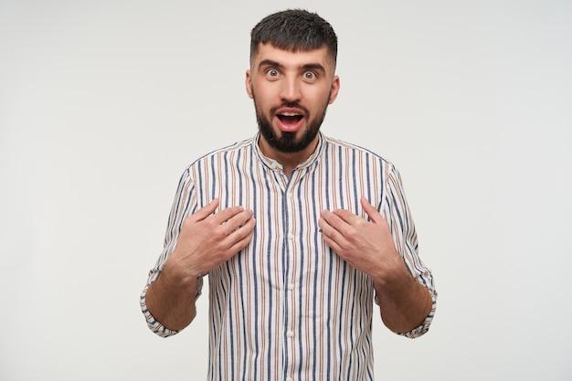 Giovane maschio castana dai capelli corti attraente sorpreso con la barba tenendo le mani sul petto e guardando con gli occhi spalancati aperti, in piedi sopra il muro bianco