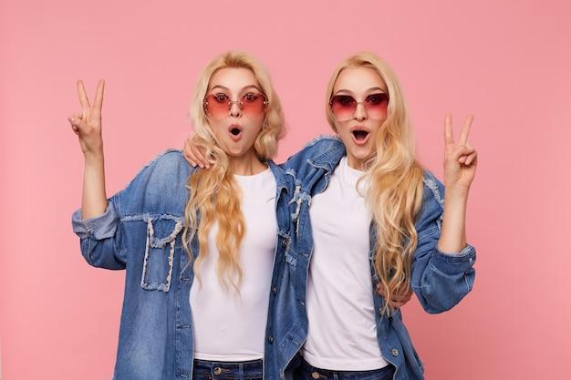 Удивленные молодые привлекательные белоголовые самки с волнистой прической, демонстрирующие жест мира и изумленно смотрящие в камеру, стоя на розовом фоне