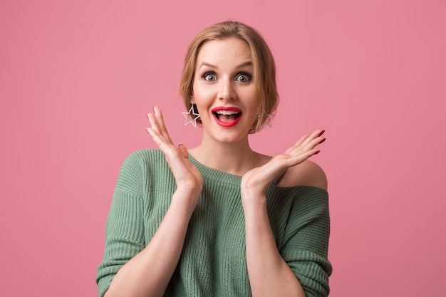Surprised young attractive woman shocked expression of face, big eyes, open mouth, hands up, funny emotion, casual style, green sweater, red lips, model posing in studio, isolated, pink background