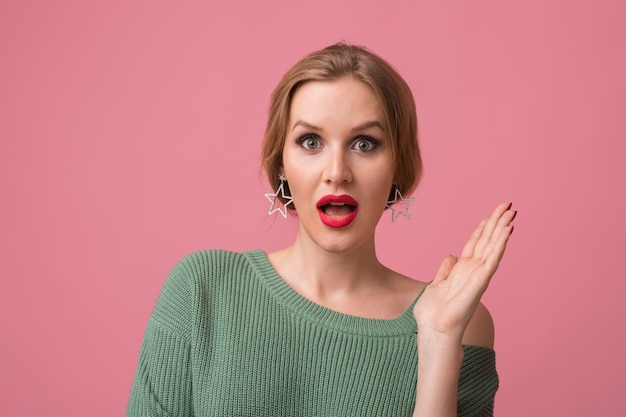 Surprised young attractive woman with shocked expression of face, open mouth, hands up, funny emotion, red lips, model posing in studio, isolated, pink background, looking in camera,