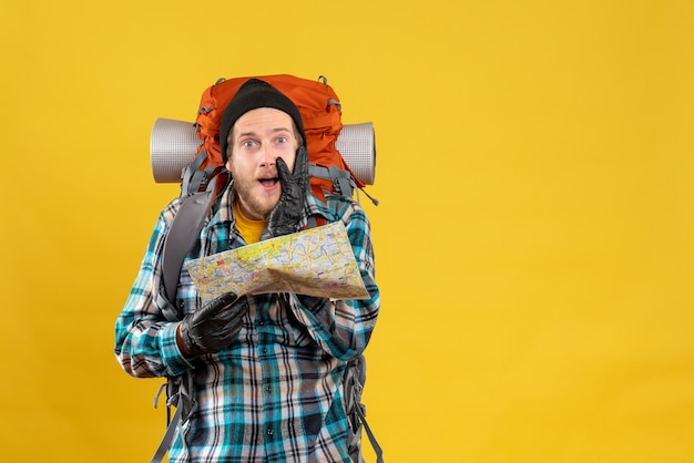 旅行地図を保持している革手袋で若いバックパッカーを驚かせた