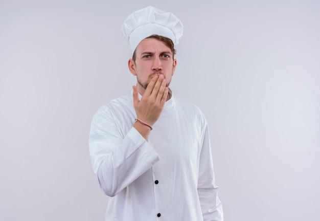 Un giovane uomo barbuto sorpreso del cuoco unico che porta l'uniforme e il cappello bianchi del fornello che tengono la mano sulla bocca mentre osservava su un muro bianco