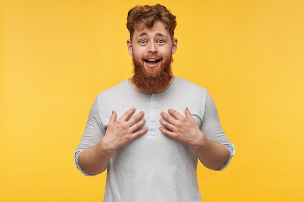 Surprised young bearded man open mouth and smiling, pointing at himself with both hands with joyful facial expression.