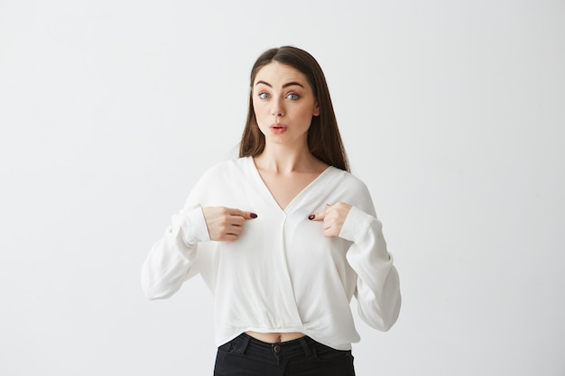 Surprised young beautiful businesswoman pointing fingers at herself .