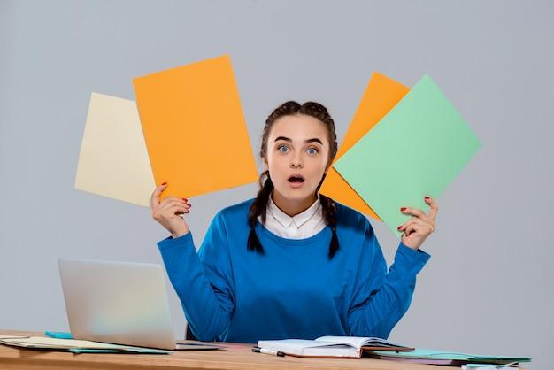 Giovane bella donna di affari sorpresa che si siede nel luogo di lavoro, tenendo le cartelle variopinte