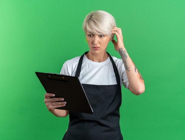 Sorpreso giovane e bella barbiere femminile in uniforme che tiene e guarda la lavagna per appunti isolata su sfondo verde