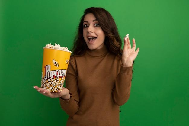 Giovane bella ragazza sorpresa che tiene secchio di popcorn con pace popcorn isolata sulla parete verde