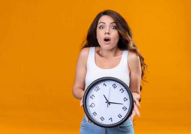 Giovane bella ragazza sorpresa che tiene orologio sulla parete arancione isolata con lo spazio della copia