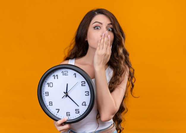 Giovane bella ragazza sorpresa che tiene l'orologio con la mano sulla bocca sulla parete arancione isolata con lo spazio della copia