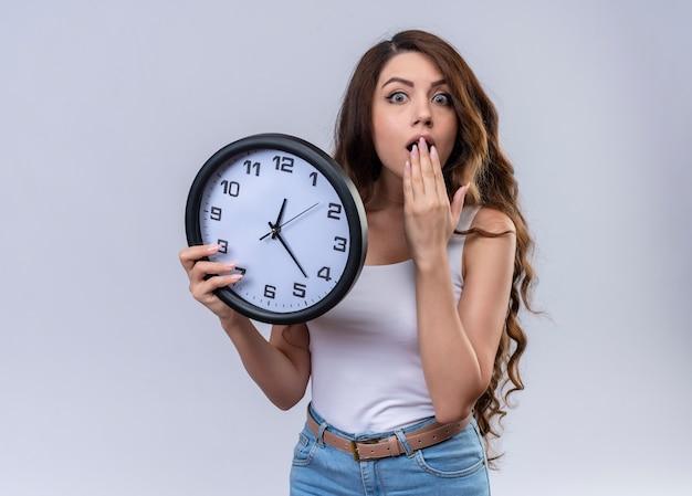 Giovane bella ragazza sorpresa che tiene l'orologio con la mano sulla bocca sulla parete bianca isolata