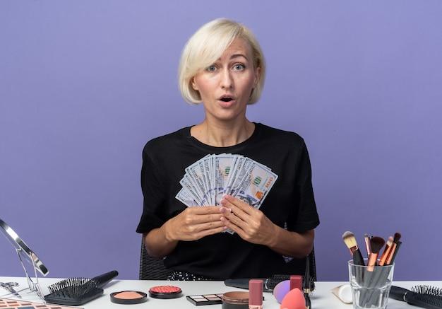 驚いた若い美しい少女は、青い背景で隔離の現金を保持している化粧ツールでテーブルに座っています。