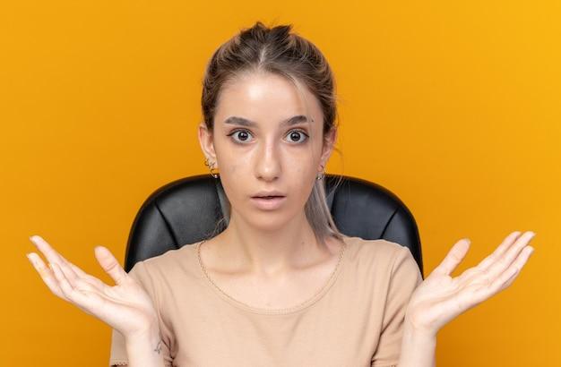 驚いた若い美しい少女は、オレンジ色の背景に分離された手を広げて化粧ツールでテーブルに座っています。