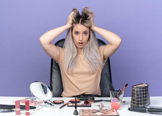 La giovane bella ragazza sorpresa si siede alla tavola con gli strumenti di trucco afferrati i capelli isolati su fondo blu
