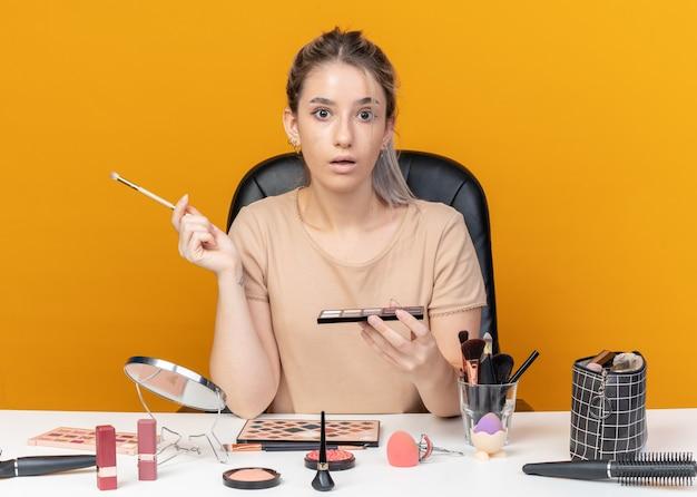 La giovane bella ragazza sorpresa si siede alla tavola con gli strumenti di trucco che tengono la tavolozza dell'ombretto con la spazzola di trucco isolata su fondo arancio