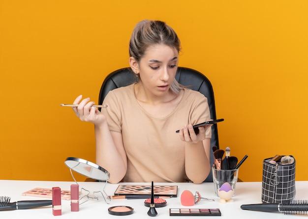 La giovane e bella ragazza sorpresa si siede al tavolo con gli strumenti per il trucco tenendo il pennello per il trucco e guardando il telefono in mano isolato su sfondo arancione