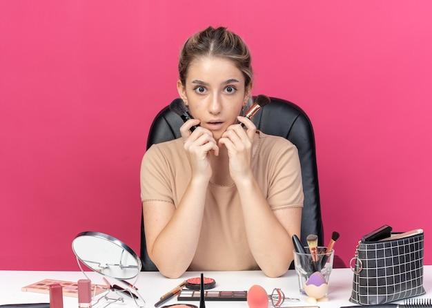 La giovane bella ragazza sorpresa si siede alla tavola con gli strumenti di trucco che tengono la spazzola della polvere isolata su fondo rosa