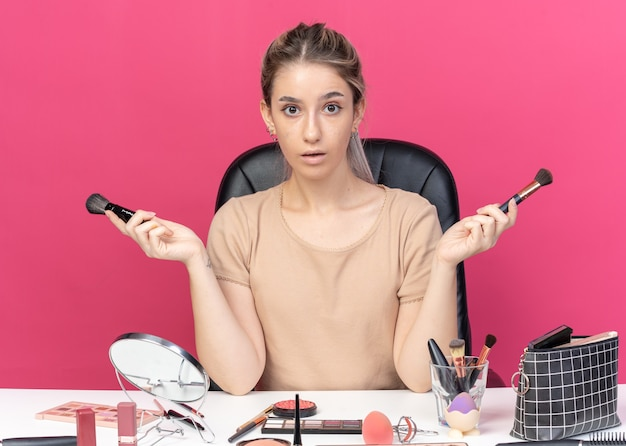 La giovane bella ragazza sorpresa si siede alla tavola con gli strumenti di trucco che tengono la spazzola della polvere che sparge le mani isolate su fondo rosa