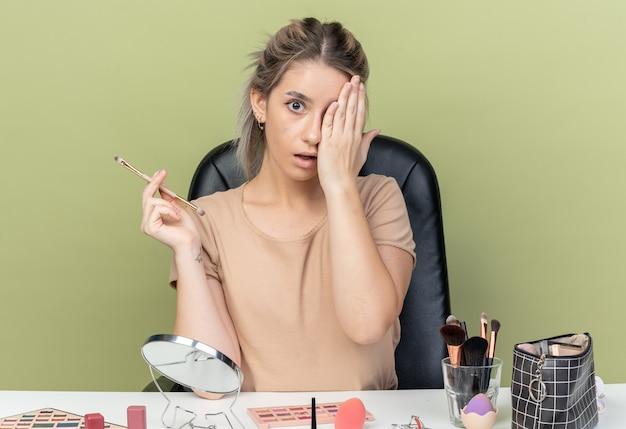 Giovane bella ragazza sorpresa che si siede allo scrittorio con gli strumenti di trucco che tengono l'occhio coperto del pennello di trucco con la mano isolata su fondo verde oliva
