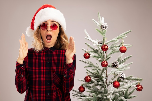 흰색 배경에 고립 된 크기를 보여주는 안경 크리스마스 모자를 쓰고 크리스마스 트리 근처에 서 놀란 젊은 아름 다운 소녀
