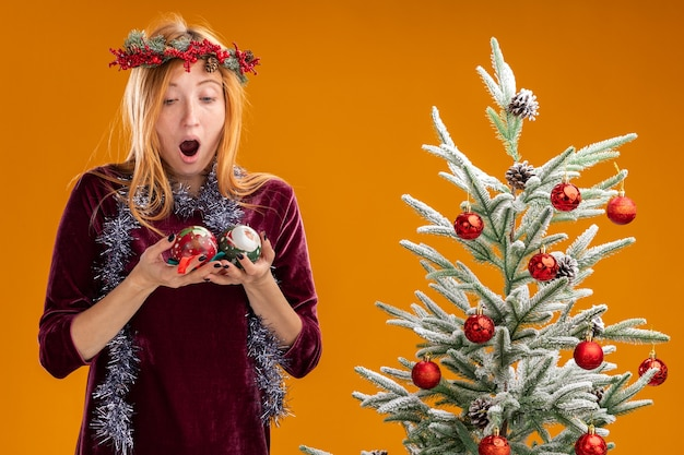 赤いドレスと花輪を身に着けているクリスマスツリーの近くに立って、オレンジ色の背景に分離されたクリスマスボールを保持し、見て驚いた若い美しい少女
