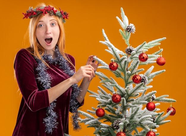オレンジ色の背景で隔離の首に花輪と赤いドレスと花輪を身に着けているクリスマスツリーの近くに立っている驚いた若い美しい少女