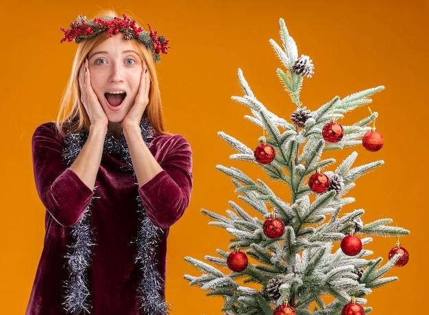 オレンジ色の背景で隔離の頬に手を置いて首に花輪と赤いドレスと花輪を身に着けているクリスマスツリーの近くに立っている驚いた若い美しい少女