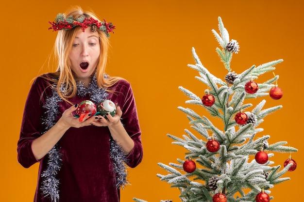 Giovane bella ragazza sorpresa che sta vicino all'albero di natale che porta vestito rosso e corona con la ghirlanda sul collo che tiene e guardando le palle di natale isolate su priorità bassa arancione