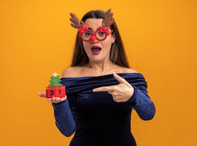 青いドレスとクリスマスグラスを持ってオレンジ色の背景で隔離のおもちゃを指して驚いた若い美しい少女
