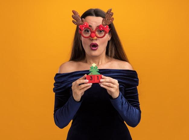 青いドレスとオレンジ色の背景で隔離のおもちゃを保持しているクリスマスのガラスを身に着けている驚いた若い美しい少女