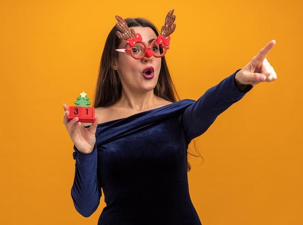 青いドレスとオレンジ色の背景で隔離の側におもちゃのポイントを保持しているクリスマスのメガネを着て驚いた若い美しい少女
