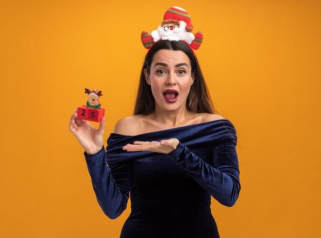 青いドレスとクリスマスの髪のフープを身に着けて、オレンジ色の背景で隔離のおもちゃを手で指して驚いた若い美しい少女