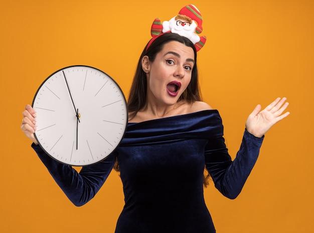 Giovane bella ragazza sorpresa che porta vestito blu e cerchio di capelli di natale che tiene l'orologio di parete che diffonde mano isolata su fondo arancio Foto Gratuite